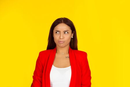 woman looking to side puzzled tongue. Woman looking to the side puzzled tongue. Mixed race model isolated on yellow background with copy space. Horizontal image. Natural, no makeup. Stock Photo
