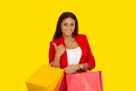 Beautiful woman showing like, thumbs up sign while holding lots of shopping bags. Mixed race model isolated on yellow background with copy space. Horizontal image. Natural, no makeup.
