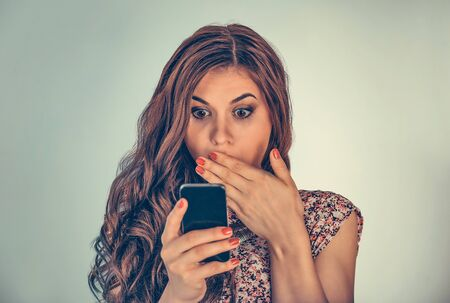 Woman looking at her phone with shocked expression on face covering mouth in shock. Mixed race model isolated on light green background with copy space. Horizontal image. Archivio Fotografico