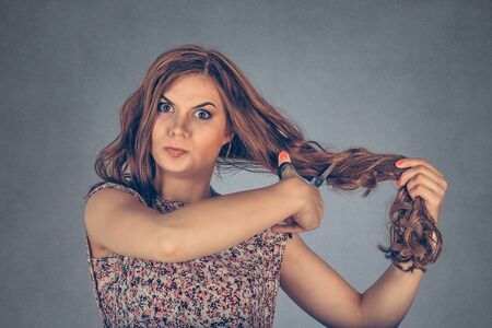 Frustrated woman holding her hair and scissors about to cut her hair looking at you camera angry. Mixed race model isolated on gray background with copy space. Horizontal image.