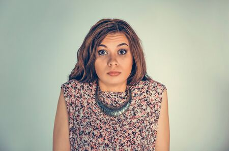Confused woman. Closeup portrait angry unhappy young person shrugging shoulders, I don't know concept isolated green wall background. Negative human emotion, facial expression, reaction body language 版權商用圖片