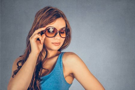 closeup portrait, confident, successful, beautiful attractive young woman, fashion girl, posing with sunglasses hand on head, isolated gray background wall. Positive human emotion, facial expression