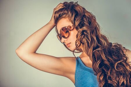 closeup portrait, confident, successful, beautiful attractive young woman, fashion girl, posing with sunglasses hand on head, isolated green background wall. Positive human emotion, facial expression