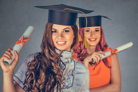 Portrait closeup beautiful happy  graduates, two graduated student girls, young women in cap gown turning smiling holding diploma scroll isolated gray background wall. Celebrating graduation ceremony Imagens