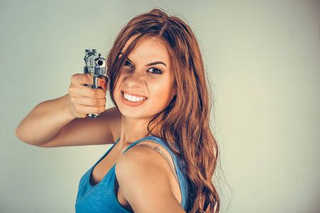 Beautiful young woman with a gun. Brunette holding Handgun looking, aimed, pointing at camera.Violent rebel gangster bandit self-justice concept. Mixed race model isolated on light green background