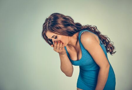 Young woman feeling nauseated about to vomit. Mixed race model in blue shirt isolated on light green background with copy space. Horizontal image.