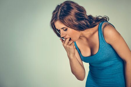 Woman sticking her fingers in her throat showing she is about to throw up, she is fed up or sick. Bulimia concept. Mixed race model isolated on light green background with copy space. Horizontal image