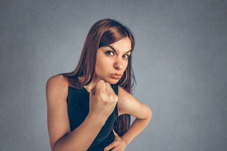 Closeup portrait angry young woman showing fist about to punch hit someone or to have nervous atomic breakdown isolated gray background. Negative human emotions facial expression feelings attitude
