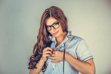 Adulterio sul posto di lavoro. Donna sexy, segretaria che indossa una camicia abbottonata formale bianca che si spoglia, guarda e civettuola. Modello di razza mista isolato su sfondo verde chiaro con copia spazio. Archivio Fotografico