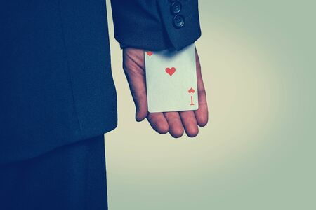 Close up of hand of a man hiding ace card in the sleeve isolated on light green yellow background. Opportunity, competition, luck, lottery, casino, chance. Banco de Imagens