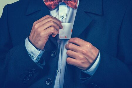 Midsection view, cropped image businessman pulling ace out of his suit, jacket isolated on green background. Play card. Opportunity, competition, luck, lottery, casino, chance, fortune Banco de Imagens