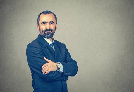 Isolated brown bearded man with suit tie blue shirt watch. Crossed arms. Serious confident entrepreneur looking to you camera. Neutral human emotion.