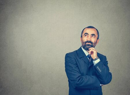 Thinking. Bearded man with dark suit tie blue shirt watch touching chin, looking up. Expressive eyes. Crossed arms. Body expression. Isolated bright green yellow wall background.