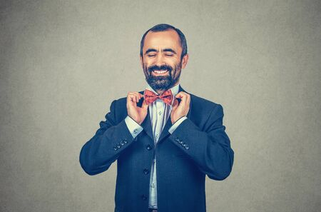Happy, bearded man with dark suit,  blue shirt, adjusting red butterfly bow, tie. Smiling, elegant manager. Positive human emotion. Accessory. Gray wall background.
