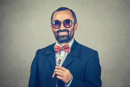 Smiling confident bearded man wears round sunglasses, holds cuban cigar. Portrait of stylish, funny guy looking you camera. Modern clothes dark suit shirt red bow tie. Positive face expression emotion