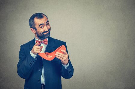 You should wear heels. Bearded businessman, man holding a red high-heeled shoe, pointing with finger to camera asking, is it yours. Half-length body. One person isolated on gray gradient background Banco de Imagens