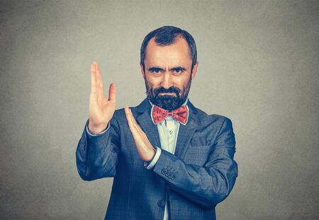 Attractive and serious adult man with beard and mustache wearing elegant suit and red bow tie shows karate chop gesture isolated on grey background Banco de Imagens