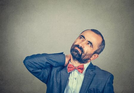 Portrait stressed, adult handsome bearded man in elegant jacket with red bow tie has bad neck pain, isolated on grey wall background. Negative human emotion facial expression Stockfoto