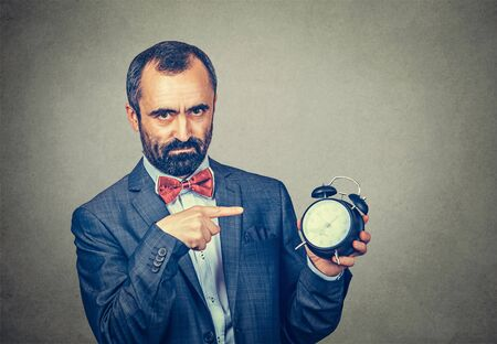 Closeup portrait serious angry annoyed frustrated adult bearded man in elegant jacket with red bow tie holding alarm clock and pointed it out, grey wall background. Human face expression body language