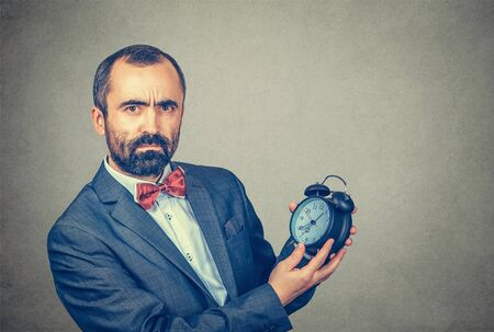 Closeup portrait serious adult bearded man in elegant jacket with red bow tie holding showing alarm clock in his hands looking at you camera, gray wall background. Human face expression, body language