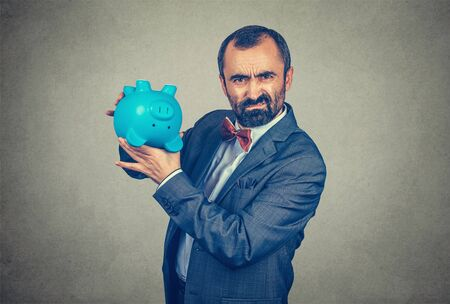 Adult displeased bearded man in elegant suit with red bow tie holding overturned piggy bank, showing its emptiness, isolated on gray wall background.