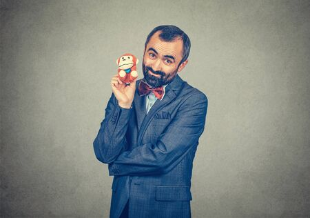 Portrait of an adult cheerful bearded man in elegant jacket with red bow tie, holding in his hand small monkey toy isolated on gray, grey background. Positive human emotion, body language