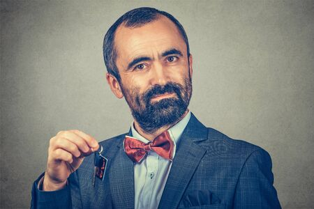 Portrait of serios bearded man, wearing elegant jacket with red bow tie and holding keys from home car office isolated on gray wall background. Human face expression