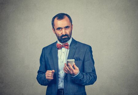 Closeup portrait serious, thoughtful bearded man wearing elegant suit with red bow tie, holding his smartphone in his hand, isolated grey wall background. Human facial expression, body language
