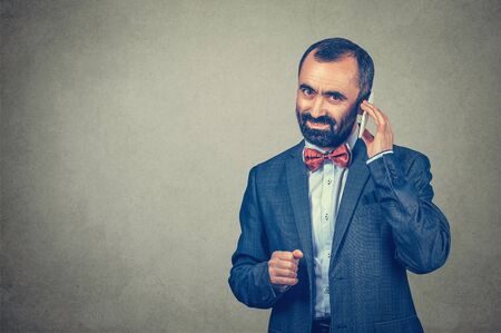 Smiling adult beared man wearing elegant suit and shirt with red bow tie, talking on mobile phone isolated on gray wall background. Positive human expression, body language