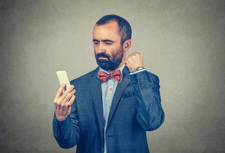 Angry bearded businessman wearing elegant suit with red bow tie, looking at his phone and clenching his fist to the cellphone, isolated gray, grey background. Negative human expression, body language Banco de Imagens