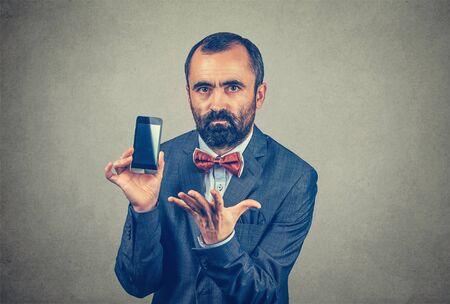 Closeup portrait bearded serious frustrated business man, wearing elegant jacket with red bow tie, showing his phone and gestured with his another hand in anger, isolated gray, grey wall background.