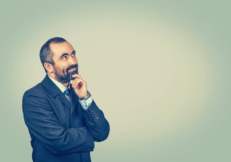 Search idea, thinking. Isolated bearded man with dark suit tie blue shirt watch touching chin, looking up away.  Crossed arms. Isolated bright green yellow wall background. Body expression.