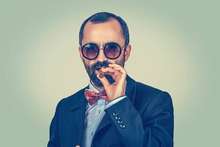Portrait of confident, rich, bearded man with round sunglasses, keeping with hand mouth smoking cuban cigar. Arrogant boss looking to you camera. Modern clothes, dark suit, blue shirt, red bow, tie. Banco de Imagens