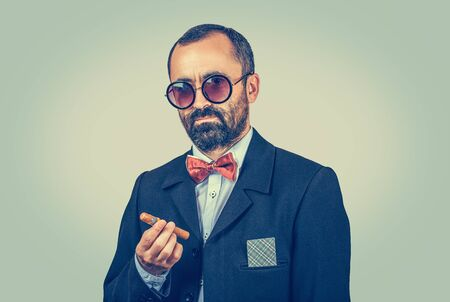 Successful, bearded man with ace, card in suit jacket pocket, holding cuban cigar isolated on green background. Serious boss with sunglasses, looking to camera. Secret, strategy, success, winner, player. Banco de Imagens
