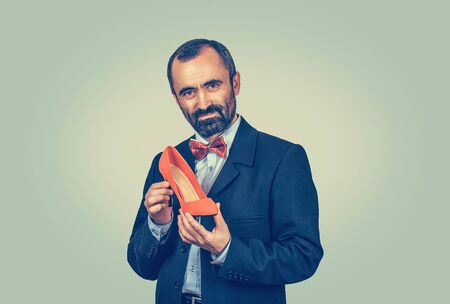 Portrait, bearded businessman in suit holding a red high-heeled shoe and looking at camera. Shoe designer concept. Half length body. One single person. Bright green yellow gradient background. Banco de Imagens