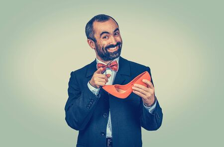 Large smiling, happy bearded man holding a red high-heeled shoe in his hand, indicating with finger it is yours. Half length body. One single person. Bright green yellow gradient background.