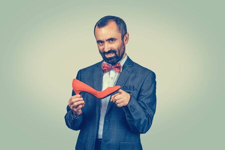 Serious bearded businessman holding a red high-heeled shoe pointing with index finger at you camera and telling it is yours. Half length body. One single person. Bright green yellow gradual background Banco de Imagens