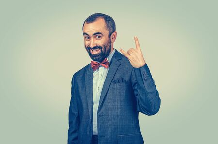 Funny bearded businessman showing heavy metal hand gesture over ligh green background. Facial expression feeling symbol, body language, non verbal communication. Banco de Imagens