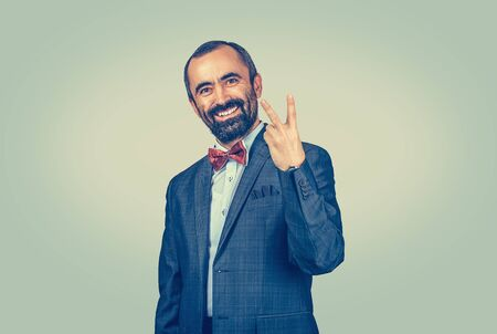 Smiling, bearded businessman showing number two, peace, victory sign with fingers hand gesture. Companion, couple, pair. Confident standing man with dark suit blue shirt red bow tie green background