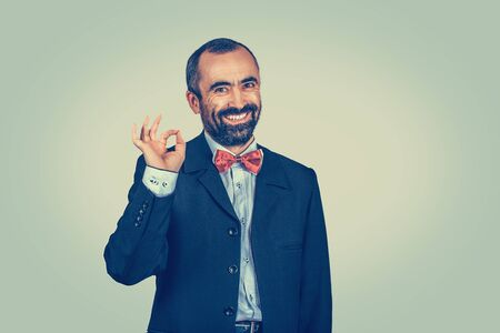 Handsome bearded man showing ok okay sign with fingers. Job done Agreement concept. Well-dressed person smiling at you camera. Human face expressions body language. Bright green-yellow wall background Banco de Imagens