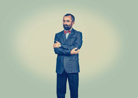 Elegant standing, bearded man with crossed arms, wearing dark suit, blue shirt, red bow, tie, looking to camera. Questioning boss, manager. Well dressed businessman. Body expression, human emotion