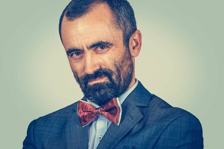 Closeup portrait bearded man looking accusatory to you camera. Human emotion face expression, body language. Businessman with suit, white shirt, red bow tie. One single person on green wall background Banco de Imagens