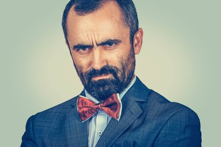 Closeup portrait angry man looking accusatory to you camera. Negative human emotion facial expression. Anger appearance. Bearded businessman in suit, white shirt, red bow tie on green wall background Banco de Imagens