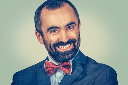 Closeup portrait, large smiling bearded man isolated on green background. Happy employer with suit, tie, blue shirt, looking at you camera. Teeth. dentistry. Positive emotion facial expression feeling Banco de Imagens