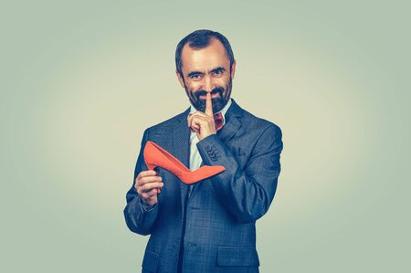 Shh. Sly bearded businessman holding a red shoe, showing hush hand gesture with finger looking at you camera. Confidentiality, privacy, secrecy, silence. Isolated on Bright green yellow background Stok Fotoğraf