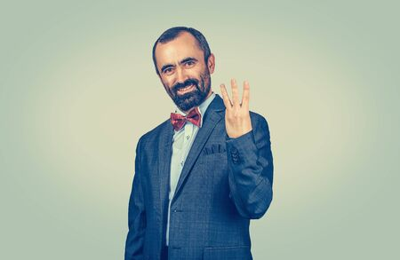 Bearded man, employee giving three fingers gesture with hand isolated on green yellow uniform background. Facial expression feeling symbol body language non verbal communication. Marketing, number