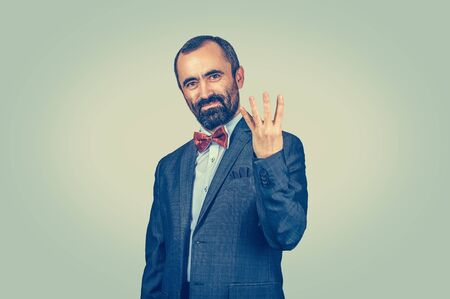 Bearded man employee giving four fingers gesture with hand isolated green yellow background. Facial expression feeling symbol body language non verbal communication. Marketing number count order price