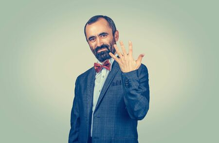 Bearded man shows five fingers gesture with hand isolated on green yellow wall background. Facial expression feeling symbol, body language, non verbal communication.