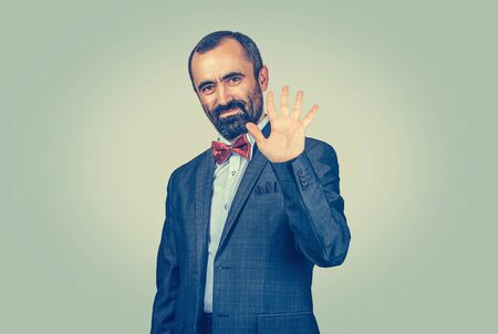 Bearded man, employee show left palm, give me five fingers gesture with hand isolated uniform background. Body language face expression non verbal communication. Ok. Job done. Number count order price