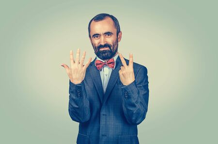 Bearded man show seven fingers gesture with hands isolated background. Facial expression feeling symbol, body language, non verbal communication. Score of competition, number, count, order, price. Banco de Imagens